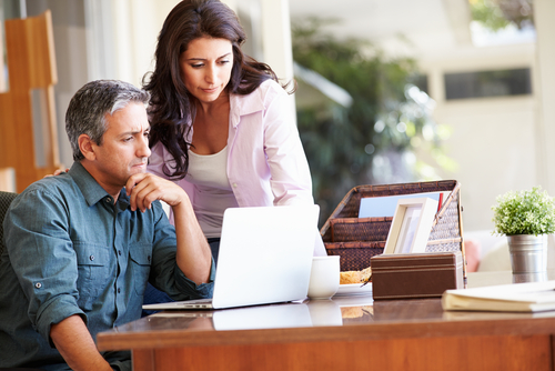 Hispanic Couple Looking at Computer in Fort Lauderdale Luxury Homes