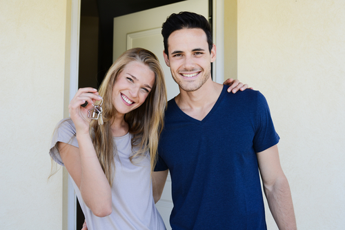 Young White Couple Outside Door of New Delray Beach Real Estate Property