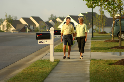 Older Couple Walking Through Neighborhood